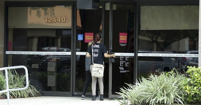 Wells Fargo's earnings fall as bank deals with scandal