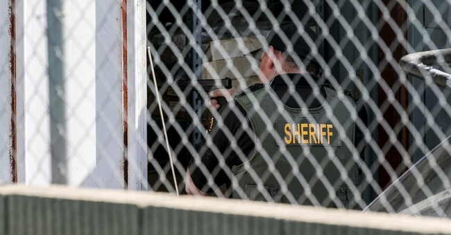 The Latest: Man sees police handcuff 1 escaped inmate