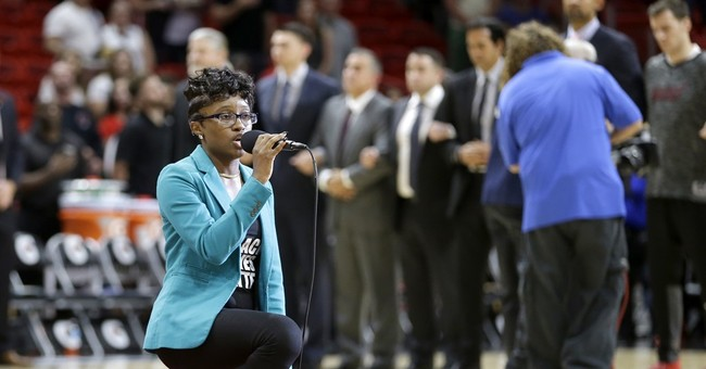 Anthem singer at Heat-76ers game kneels during performance