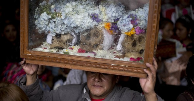 Bolivians carry human skulls asking for favors in festival