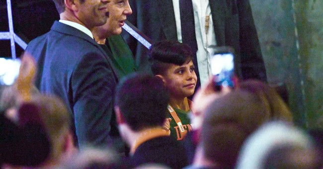 Germany's Merkel thanked by Afghan boy at party meeting
