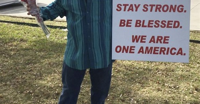 Dallas man holds sign of support outside Islamic center