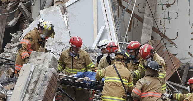 Firefighter held hand of woman buried under building