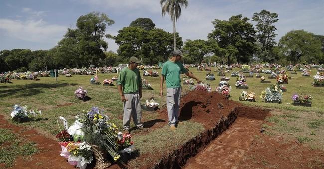 Rain and sorrow accentuate memorial for dead at Brazil club