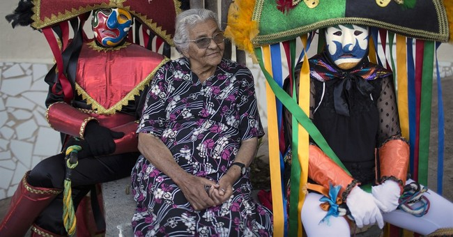 Frowning masks and whips highlight Carnival in Brazil town