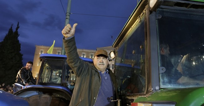 Protesting Greek farmers drive tractors through Athens