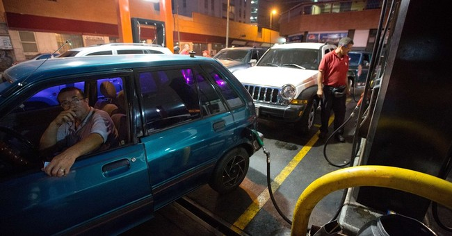 Economically struggling Venezuela hikes gas prices, devalues
