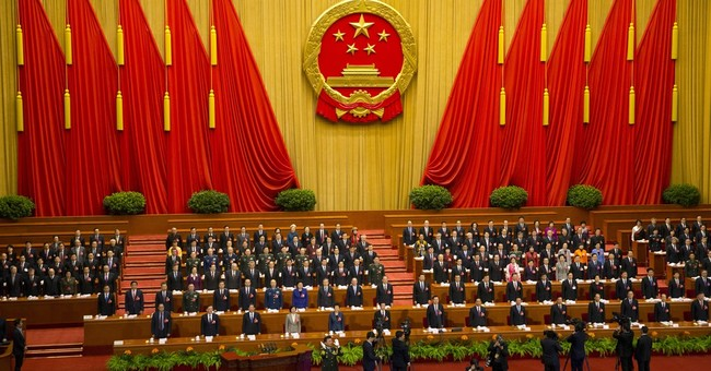 China tries to reassure on economy, cuts growth target