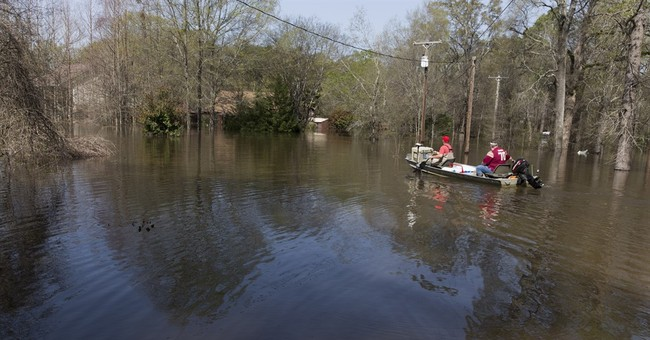 The Latest: Guard members help transform sidewalk into levee