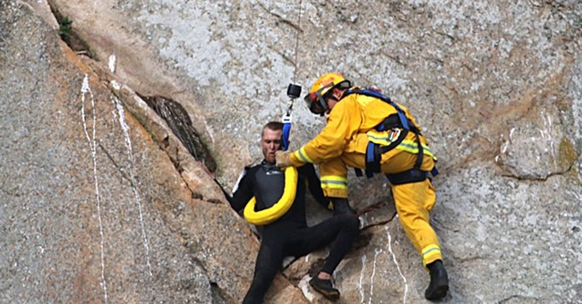 The Latest: Man who scaled cliff to propose later arrested