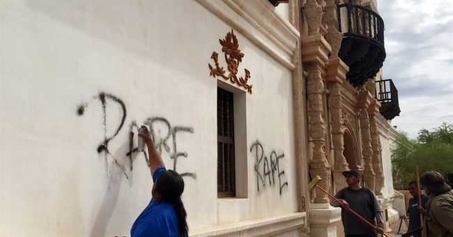 Workers removing graffiti from exterior of historic mission