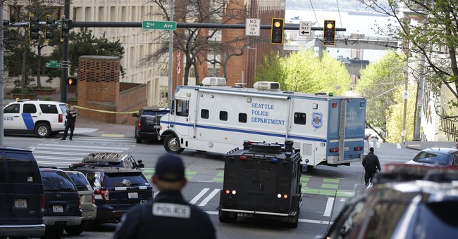 The Latest: 3 officers wounded by gunfire after robbery