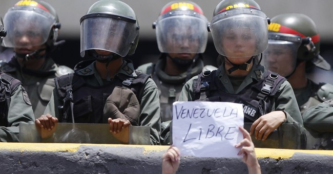 Roses in hand, Venezuelan women protesters face security forces