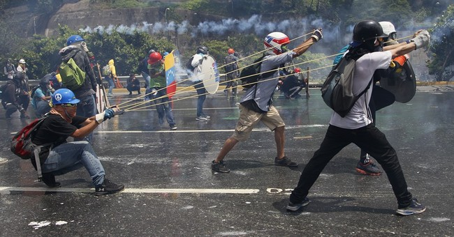 Venezuelans battle with shields, gas masks, fecal bombs