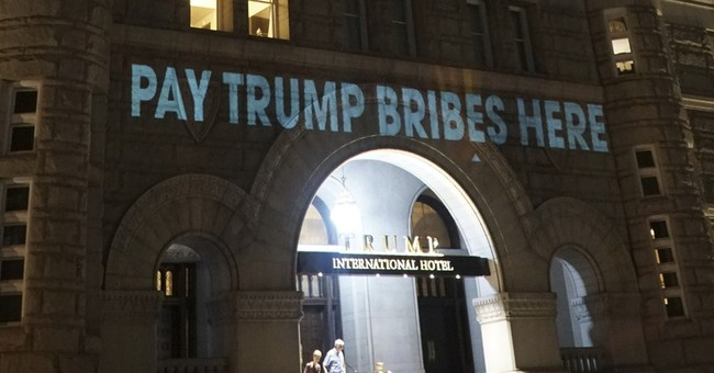 Artist projects words 'pay Trump bribes here' onto DC hotel