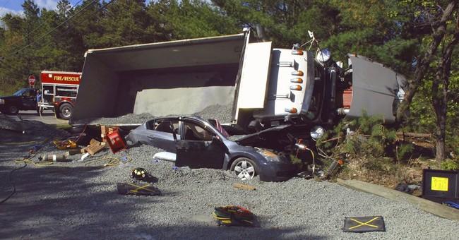Dump truck overturns onto car, burying it in stones