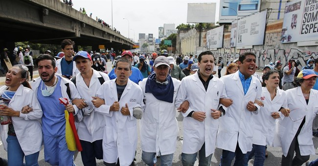 Angry Venezuela protesters take aim at Chavez statues, home