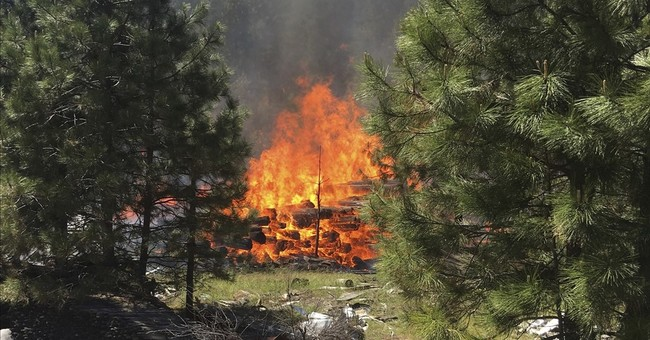 The Latest: Fire about 50 percent contained at tourism spot