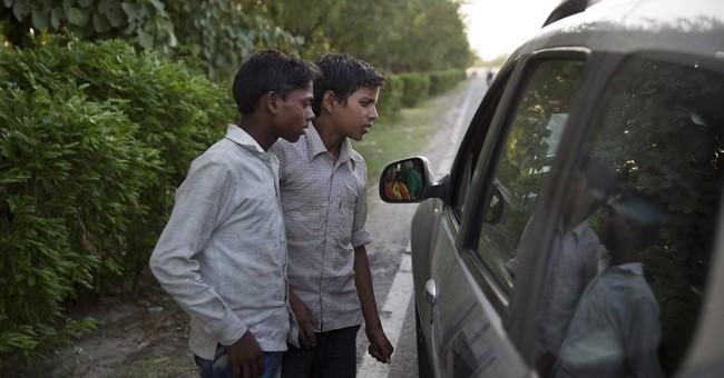 Hardscrabble children sell corn in the heat by India's roads