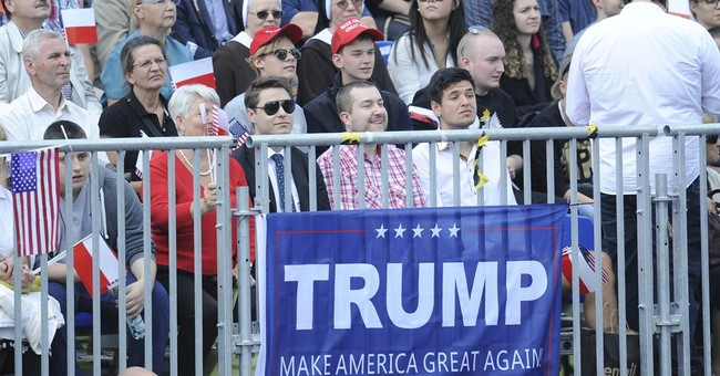 Trump welcomed by cheering, flag-waving supporters in Warsaw
