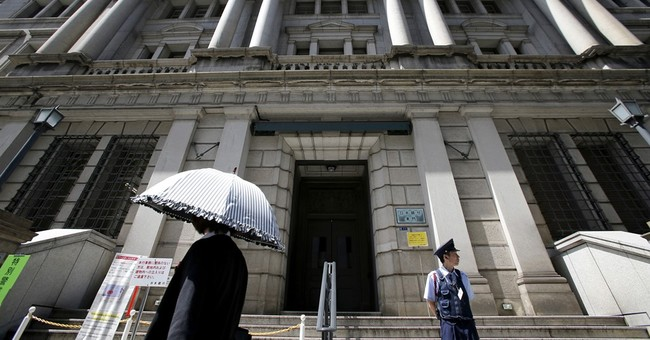 Bank of Japan keeps stimulus intact, cuts inflation outlook