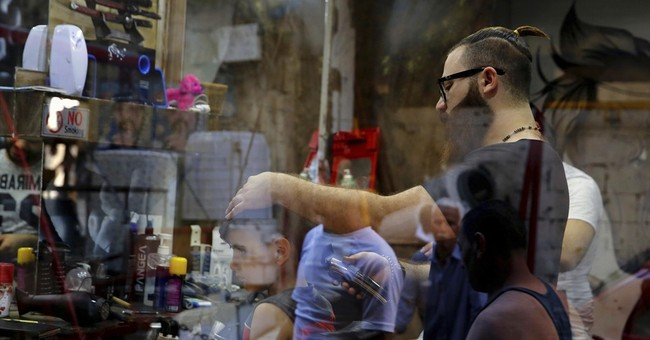 Syrian barber creates portraits on canvas _  clients' heads