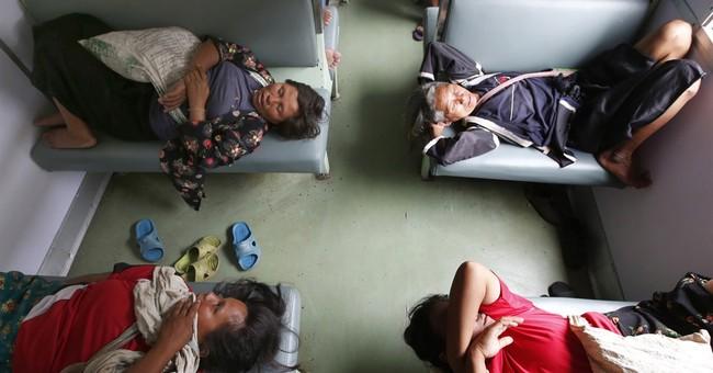 Image of Asia: Passengers sleep on Bangkok train