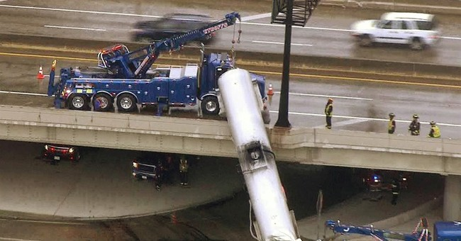 Tanker left dangling from overpass after interstate crash