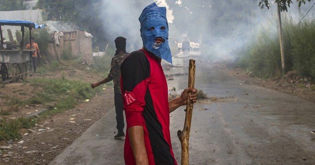 Image of Asia: Masked protester carries stick and stone