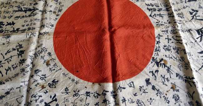 The Latest: WWII vet arrives in Tokyo with battlefield flag
