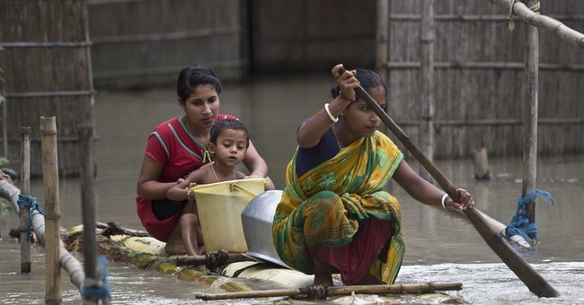 Image of Asia: Flooded villagers paddle for drinking water