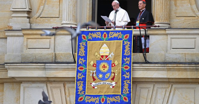 The Latest: Crowds gather beneath rain for papal Mass