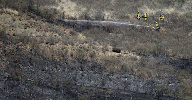 California firefighters hose down blaze ahead of wind gusts