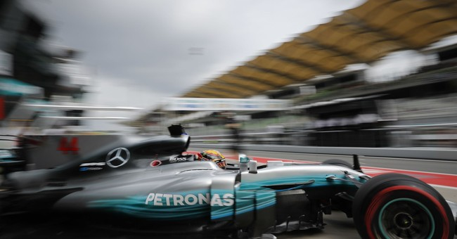 Image of Asia: Mercedes driver Hamilton steers out of garage