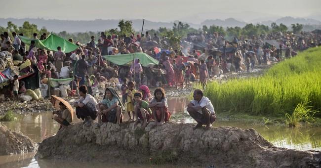 The Latest: Amnesty says Myanmar killed 100s of Rohingya