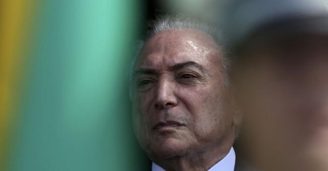 The Latest: Brazilian president reported hospitalized