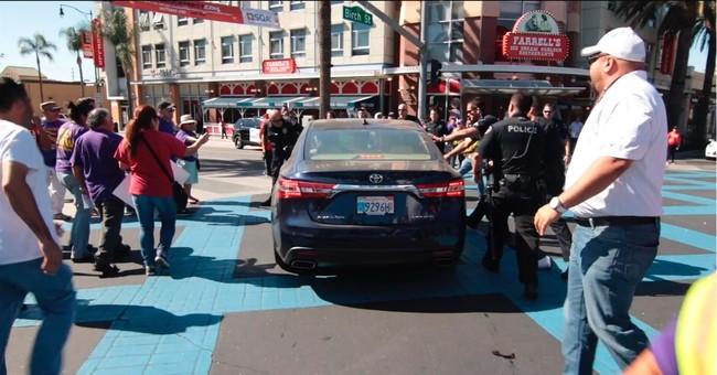 Car drives into immigration protest; motorist arrested