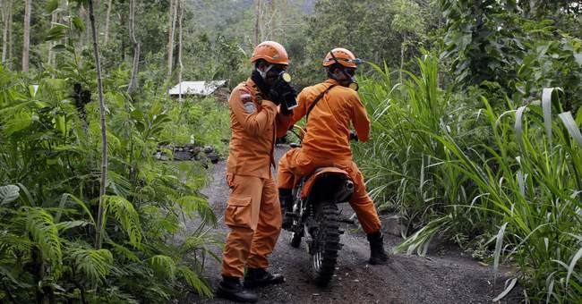 Thousands flee Bali volcano but some stay put or run to it