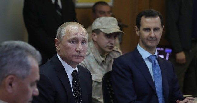 Putin declares victory on visit to air base in Syria