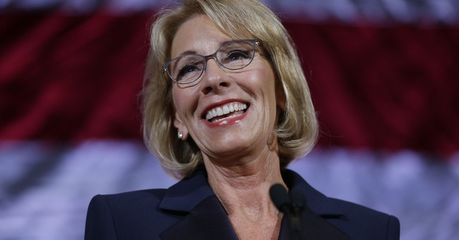 The Latest: Some in graduation crowd boo, turn from DeVos