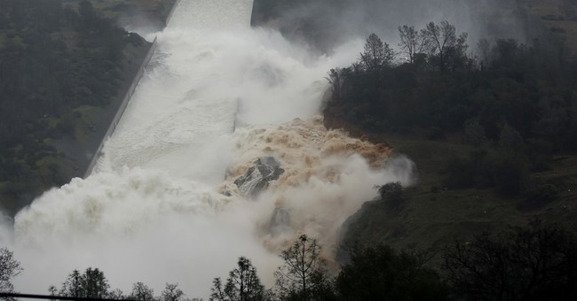 Water flowing over emergency spillway at tallest US dam