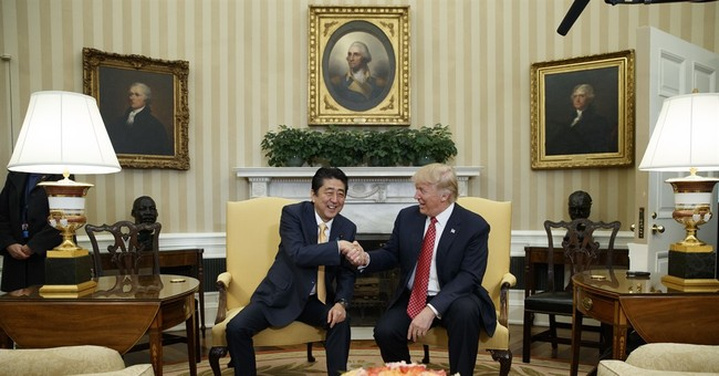 Smiles, a hug set tone for Trump's meeting with Japan's Abe