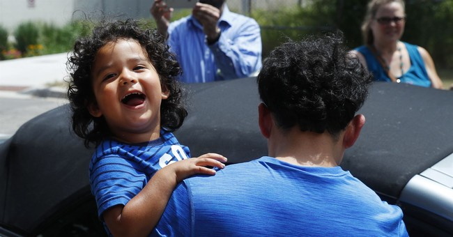 Reunited immigrant children scooped up into parents' arms