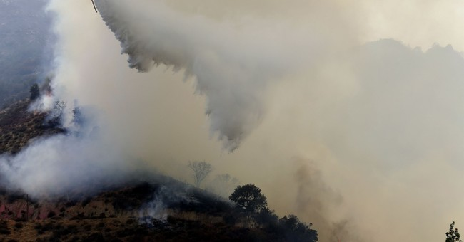 Crews battle growing wildfire near homes in California