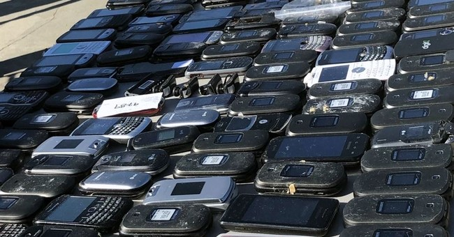 Unable to jam signals, prison pays cops to fight cellphones