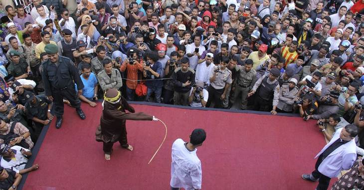 An Islamic Shariah law official whips a man convicted of gambling with a rattan cane watched by people inside a mosque compound in Banda Aceh, Aceh Province, Indonesia, Friday, Sept. 19