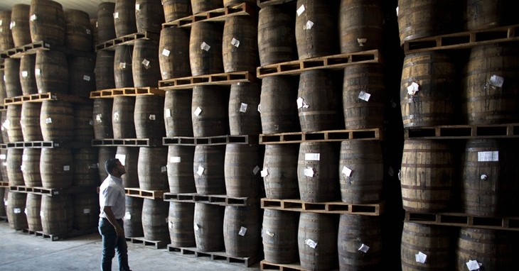 In this Thursday, March 26, 2015 photo, Jhorgen Romero, Head of Processing and Aging at Santa Teresa looks at the barrels filled with rum at the Santa Teresa rum factory in La Victoria,