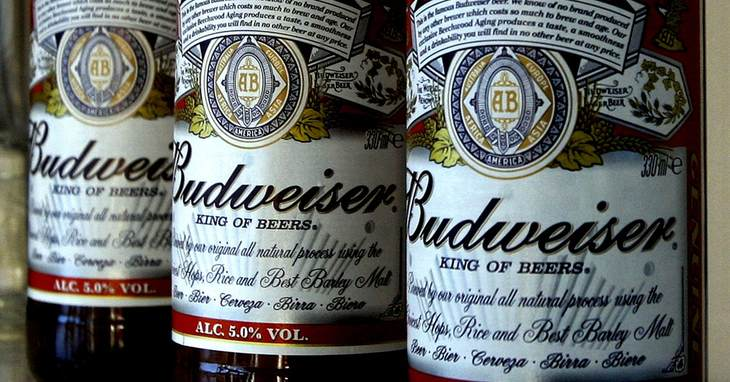 FILE - This Jan. 27, 2009 file photo shows bottles of Budweiser beer at the Stag Brewery in London. Anheuser-Busch is bringing back its canine and Clydesdales combo this Super Bowl, hop