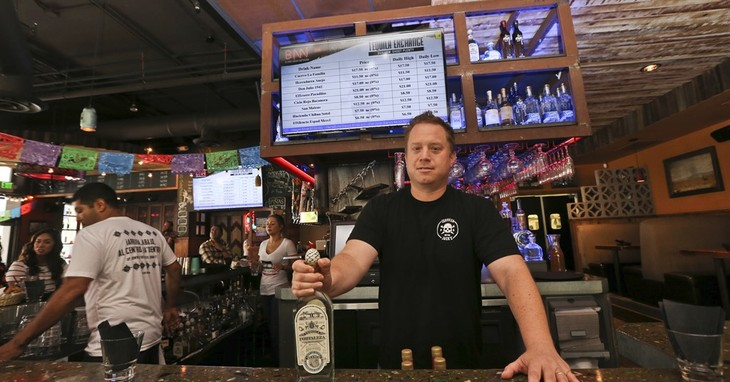 In this Thursday, May 5, 2016, photo, Frank Miller, a partner in a series of eight bars in San Diego, shows off some of the tequila collection at The Blind Burro, in San Diego, where th